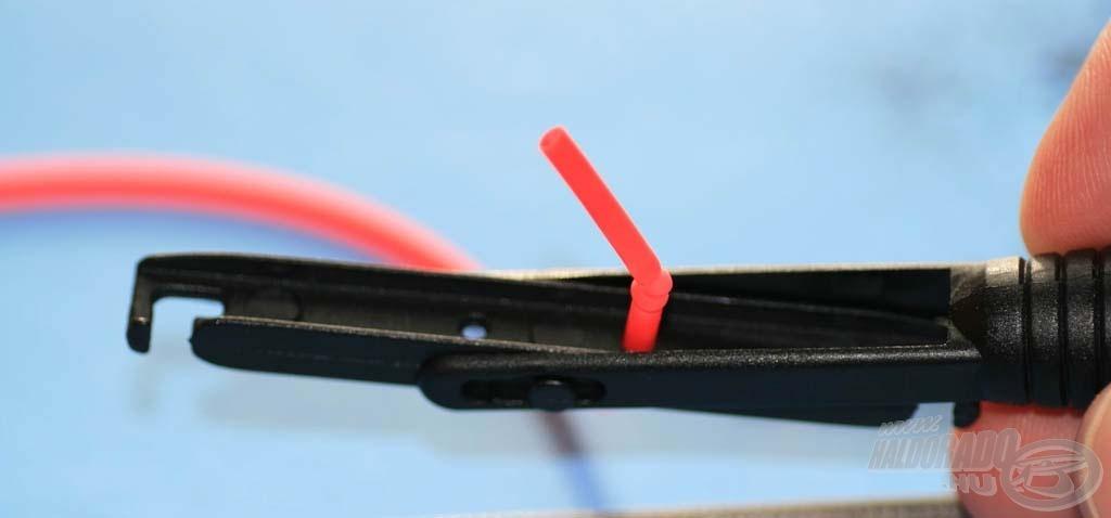 A gumit a befűző dróttal végigfűzzük a második tagon is, majd egy picit megfeszítve elvágjuk, és felhúzzuk rá a gumirögzítő kúp létra végét. Ide kell kötni egy csomót, majd a felesleget levágni, ez fogja meggátolni a kicsúszását